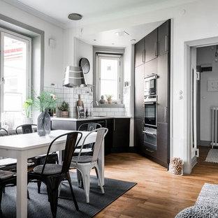 Inspiration för ett mellanstort minimalistiskt kök, med släta luckor, svarta skåp, vitt stänkskydd och mellanmörkt trägolv