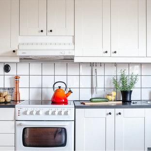 Nordisk inredning av ett mellanstort l-kök, med en nedsänkt diskho, skåp i shakerstil, vita skåp, vitt stänkskydd, stänkskydd i keramik och vita vitvaror