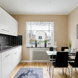Small scandinavian eat-in kitchen inspiration - Eat-in kitchen - small scandinavian single-wall light wood floor eat-in kitchen idea in Gothenburg with a drop-in sink, flat-panel cabinets, white cabinets, black backsplash, no island, granite countertops and white appliances