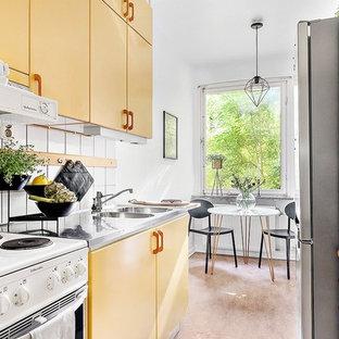 ストックホルムの中サイズの北欧スタイルのおしゃれなキッチン (ダブルシンク、フラットパネル扉のキャビネット、黄色いキャビネット、ステンレスカウンター、白いキッチンパネル、セラミックタイルのキッチンパネル、白い調理設備、アイランドなし) の写真