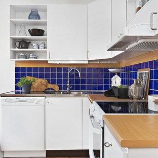 Idéer för att renovera ett litet nordiskt beige beige kök, med träbänkskiva, blått stänkskydd, en integrerad diskho, släta luckor, vita skåp, vita vitvaror, ljust trägolv och beiget golv