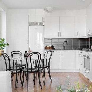 Inspiration för ett skandinaviskt kök, med släta luckor, vita skåp, svart stänkskydd, vita vitvaror, ljust trägolv och brunt golv