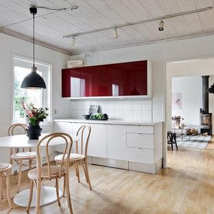 Bild på ett mellanstort nordiskt linjärt kök och matrum, med släta luckor, röda skåp, vitt stänkskydd, mellanmörkt trägolv och beiget golv