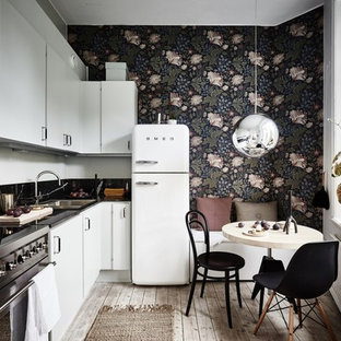 Photo of a mid-sized scandinavian l-shaped eat-in kitchen in Gothenburg with flat-panel cabinets, white cabinets, white appliances, light hardwood floors, no island and a double-bowl sink.