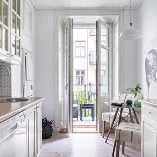 Foto på ett litet nordiskt kök, med en enkel diskho, luckor med profilerade fronter, vita skåp, träbänkskiva, flerfärgad stänkskydd och ljust trägolv