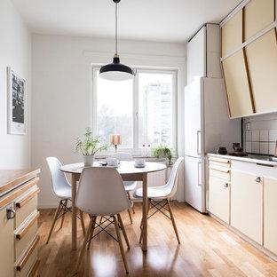 Idéer för att renovera ett mellanstort skandinaviskt parallellkök, med släta luckor, gula skåp, vita vitvaror, en integrerad diskho, bänkskiva i rostfritt stål, vitt stänkskydd och ljust trägolv