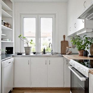 Inspiration för avskilda nordiska brunt u-kök, med en integrerad diskho, släta luckor, vita skåp, träbänkskiva, vitt stänkskydd, stänkskydd i keramik, vita vitvaror, mellanmörkt trägolv och beiget golv