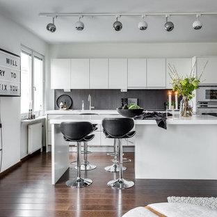 Bild på ett funkis kök med öppen planlösning, med en undermonterad diskho, släta luckor, vita skåp, grått stänkskydd, vita vitvaror, mörkt trägolv och en köksö