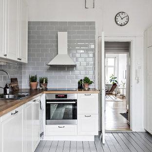 Bild på ett litet nordiskt kök, med vita skåp, en dubbel diskho, luckor med upphöjd panel, träbänkskiva, grått stänkskydd, stänkskydd i tunnelbanekakel, målat trägolv och grått golv