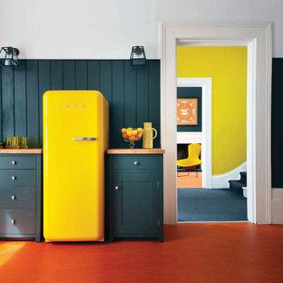 ストックホルムの広いミッドセンチュリースタイルのおしゃれなキッチン (フラットパネル扉のキャビネット、緑のキャビネット、木材カウンター、緑のキッチンパネル、木材のキッチンパネル、カラー調理設備、リノリウムの床、アイランドなし、オレンジの床) の写真