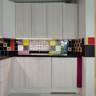 ストックホルムの小さいエクレクティックスタイルのおしゃれなI型キッチン (マルチカラーのキッチンパネル、セメントタイルのキッチンパネル、淡色無垢フローリング、グレーの床、黒いキッチンカウンター) の写真
