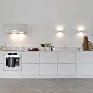 Inspiration för skandinaviska linjära grått kök, med en undermonterad diskho, släta luckor, vita skåp, grått stänkskydd, vita vitvaror, ljust trägolv och beiget golv