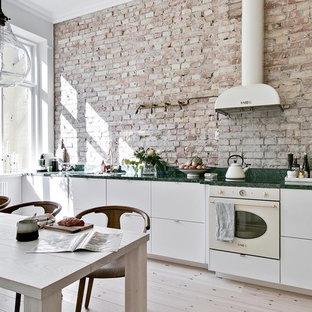 Exempel på ett stort minimalistiskt grön linjärt grönt kök och matrum, med släta luckor, vita skåp, marmorbänkskiva, beige stänkskydd, stänkskydd i tegel, vita vitvaror, ljust trägolv och beiget golv