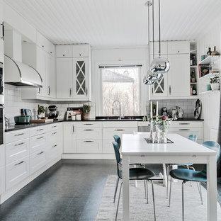 Неиссякаемый источник вдохновения для домашнего уюта: угловая кухня в скандинавском стиле с обеденным столом, фасадами с утопленной филенкой, белыми фасадами, столешницей из оникса, белым фартуком, полом из линолеума, серым полом, врезной раковиной, фартуком из плитки кабанчик и техникой из нержавеющей стали без острова