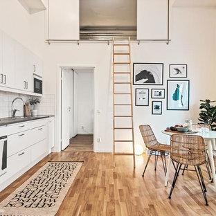 Bild på ett nordiskt grå linjärt grått kök och matrum, med släta luckor, vita skåp, vitt stänkskydd, vita vitvaror, ljust trägolv och beiget golv