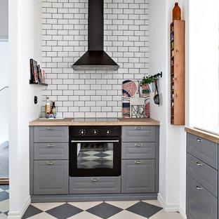 Foto på ett avskilt, litet nordiskt kök, med grå skåp, träbänkskiva, vitt stänkskydd, stänkskydd i tunnelbanekakel, svarta vitvaror, flerfärgat golv, linoleumgolv och luckor med upphöjd panel