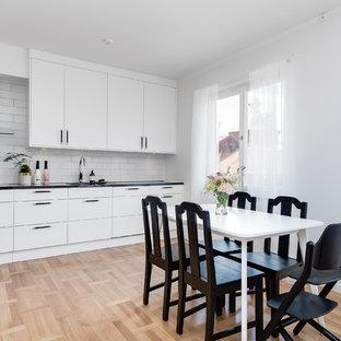 Inredning av ett skandinaviskt mellanstort linjärt kök och matrum, med släta luckor, vita skåp, vitt stänkskydd, stänkskydd i tunnelbanekakel och ljust trägolv