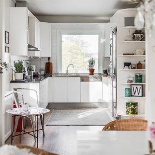 Idéer för avskilda minimalistiska u-kök, med släta luckor, vita skåp, vitt stänkskydd, integrerade vitvaror, mörkt trägolv och brunt golv