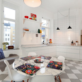 Small eclectic eat-in kitchen inspiration - Small eclectic single-wall ceramic floor eat-in kitchen photo in Stockholm with flat-panel cabinets, white cabinets, marble countertops, white backsplash, ceramic backsplash, black appliances and no island