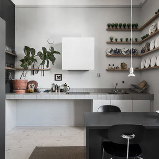 Mid-sized scandinavian single-wall eat-in kitchen in Stockholm with open cabinets, tile benchtops, white splashback, light hardwood floors and no island.