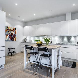 Idéer för att renovera ett mellanstort funkis beige linjärt beige kök, med släta luckor, vita skåp, träbänkskiva, grått stänkskydd, stänkskydd i marmor, integrerade vitvaror, en köksö, beiget golv och ljust trägolv
