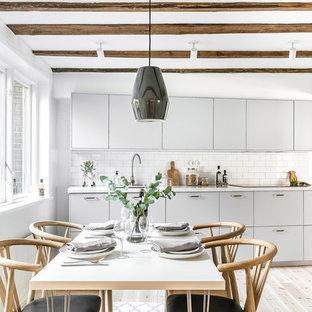 Idéer för att renovera ett skandinaviskt kök, med släta luckor, vita skåp, granitbänkskiva, vitt stänkskydd och ljust trägolv