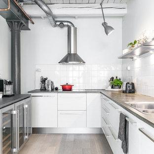 Foto på ett industriellt kök, med en dubbel diskho, släta luckor, vita skåp, vitt stänkskydd, rostfria vitvaror, ljust trägolv och beiget golv