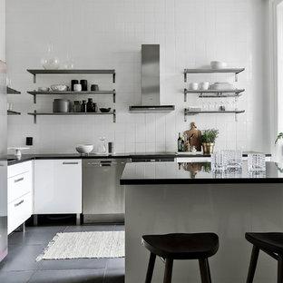 Bild på ett nordiskt kök, med vita skåp, vitt stänkskydd, en köksö och grått golv