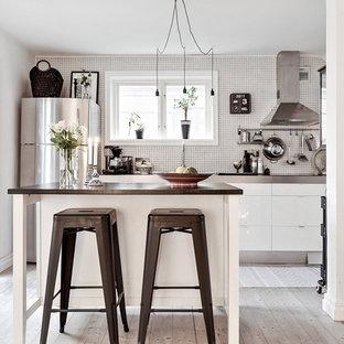 Inspiration för små minimalistiska parallellkök, med släta luckor, vita skåp, vitt stänkskydd, ljust trägolv, en köksö, beiget golv, bänkskiva i rostfritt stål och rostfria vitvaror