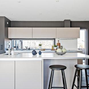 Modern inredning av ett linjärt kök med öppen planlösning, med släta luckor, vita skåp, rostfria vitvaror, en köksö och svart golv