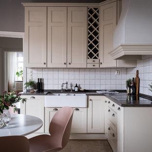 Exempel på ett minimalistiskt svart svart kök, med en rustik diskho, luckor med infälld panel, beige skåp, vitt stänkskydd och beiget golv