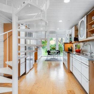 Idéer för att renovera ett skandinaviskt kök, med en integrerad diskho, släta luckor, vita skåp, bänkskiva i rostfritt stål, grått stänkskydd, stänkskydd i mosaik, rostfria vitvaror, ljust trägolv och beiget golv