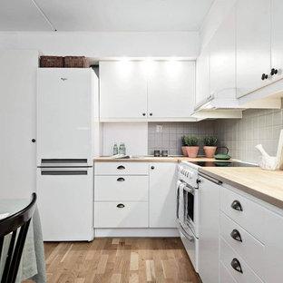 Idéer för ett minimalistiskt beige kök, med en nedsänkt diskho, släta luckor, vita skåp, träbänkskiva, grått stänkskydd, vita vitvaror, mellanmörkt trägolv och brunt golv
