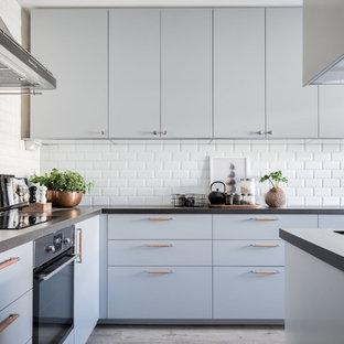 Minimalistisk inredning av ett grå grått l-kök, med släta luckor, grå skåp, vitt stänkskydd, stänkskydd i tunnelbanekakel och grått golv