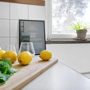 Small eclectic enclosed kitchen pictures - Example of a small eclectic l-shaped light wood floor and beige floor enclosed kitchen design in Stockholm with a double-bowl sink, flat-panel cabinets, white cabinets, stainless steel countertops, white backsplash, porcelain backsplash and white appliances