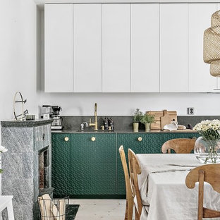 Design ideas for a mid-sized scandinavian single-wall open plan kitchen in Stockholm with a single-bowl sink, beaded inset cabinets, green cabinets, granite benchtops, black splashback, panelled appliances, light hardwood floors, no island and beige floor.