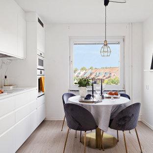 Foto på ett minimalistiskt vit linjärt kök och matrum, med släta luckor, vita skåp, vitt stänkskydd, stänkskydd i sten, vita vitvaror, ljust trägolv och beiget golv
