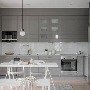 Inspiration för ett nordiskt vit vitt kök, med en undermonterad diskho, grå skåp, vitt stänkskydd, stänkskydd i tunnelbanekakel, rostfria vitvaror och ljust trägolv