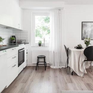 Exempel på ett litet nordiskt grå linjärt grått kök med öppen planlösning, med släta luckor, vita skåp, laminatbänkskiva, vitt stänkskydd, stänkskydd i porslinskakel och vita vitvaror