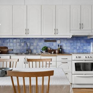 Inspiration för nordiska linjära brunt kök och matrum, med en integrerad diskho, luckor med upphöjd panel, vita skåp, träbänkskiva, blått stänkskydd, vita vitvaror, mellanmörkt trägolv och brunt golv