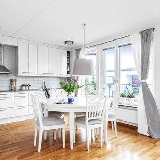 Inredning av ett skandinaviskt mellanstort kök och matrum, med mellanmörkt trägolv, släta luckor, vita skåp och grått stänkskydd