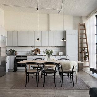 Idéer för att renovera ett nordiskt grå grått kök, med skåp i shakerstil, blå skåp, vitt stänkskydd, stänkskydd i tunnelbanekakel, rostfria vitvaror, mellanmörkt trägolv och brunt golv