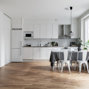 Bild på ett mellanstort skandinaviskt grå linjärt grått kök och matrum, med en trippel diskho, släta luckor, vita skåp, vitt stänkskydd, stänkskydd i porslinskakel, rostfria vitvaror, mellanmörkt trägolv och brunt golv