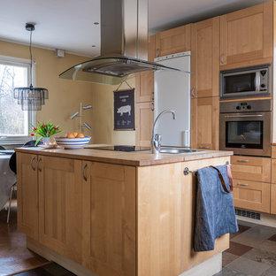 Bild på ett minimalistiskt kök och matrum, med en enkel diskho, luckor med infälld panel, skåp i ljust trä, träbänkskiva, rostfria vitvaror, en köksö och flerfärgat golv