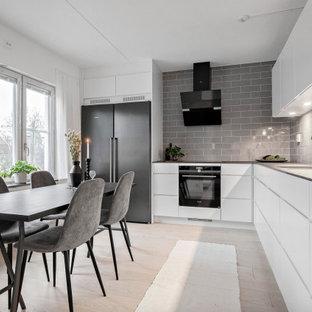 Bild på ett mellanstort minimalistiskt grå grått kök, med en enkel diskho, släta luckor, vita skåp, laminatbänkskiva, grått stänkskydd, stänkskydd i porslinskakel, rostfria vitvaror och beiget golv