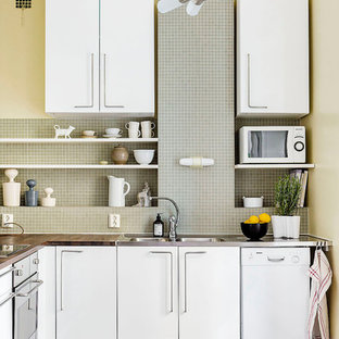 Small contemporary eat-in kitchen photos - Inspiration for a small contemporary l-shaped limestone floor eat-in kitchen remodel in Stockholm with a double-bowl sink, flat-panel cabinets, white cabinets, wood countertops, gray backsplash, white appliances and no island