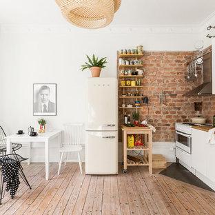 Cette photo montre une petite cuisine américaine linéaire scandinave avec un évier posé, un placard à porte plane, des portes de placard blanches, un plan de travail en bois, un électroménager blanc, un sol en bois clair et un îlot central.