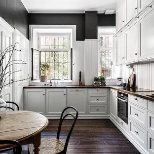 Idéer för vintage kök, med en nedsänkt diskho, skåp i shakerstil, grå skåp, vitt stänkskydd, svarta vitvaror och mörkt trägolv