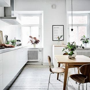 Einzeilige, Große Nordische Wohnküche mit integriertem Waschbecken, flächenbündigen Schrankfronten, weißen Schränken, Edelstahl-Arbeitsplatte und gebeiztem Holzboden in Göteborg