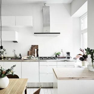 Aménagement d'une petite cuisine américaine linéaire scandinave avec un évier 1 bac, un placard à porte plane, des portes de placard blanches, un plan de travail en inox, un électroménager blanc, un sol en bois peint et un îlot central.